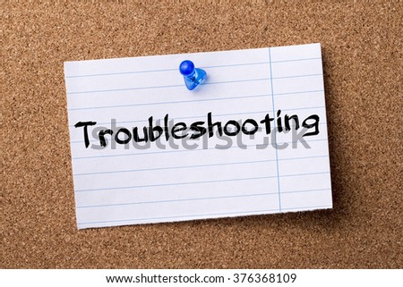 Troubleshooting - teared note paper  pinned on bulletin board - horizontal image - stock photo