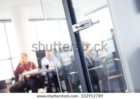 Trough glass door view of corporate meeting. Business and Entrepreneurship concept. Fockus on door. Unrecognizable people in the background. - stock photo