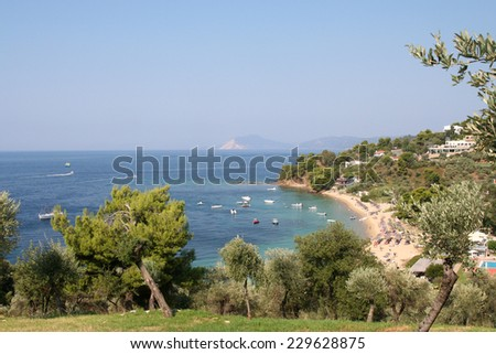 Troulos Bay. A beautiful, idyllic beach and bay on the romantic Greek island of Skiathos. Boats lie close to shore, in the inviting water of the blue Mediterranean Sea.