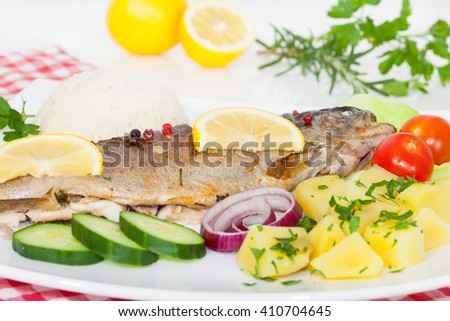 Trout fish baked with potatoes, lemon, spices and herbs - stock photo
