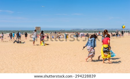 TROUVILLE, FRANCE - JUN 7, 2015:  Unidentified tourists on the coast of Trouville, Normandy, France. Trouville is a village of fishermen and a popular tourist attraction in Normandy
