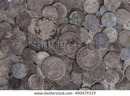 trove of ancient medieval coins silver background - stock photo