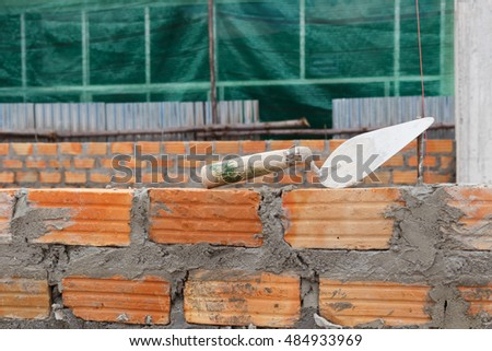 Trowel and bricks wall on construction site.