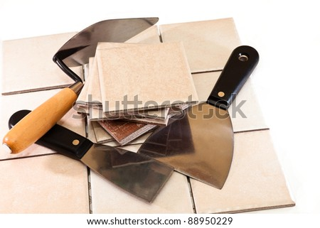 trowel and spatula against the fragments of ceramic tiles - stock photo