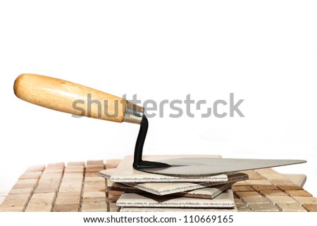 Trowel on a ceramic tile on a white background - stock photo