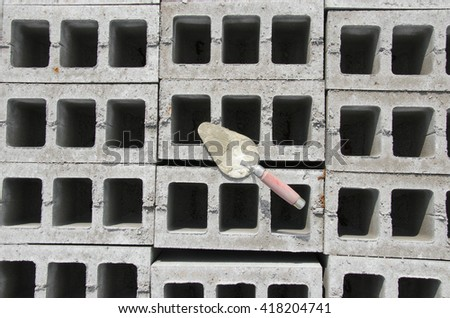 Trowel on cinder block gray background. against the background of the brickwork is trowel. - stock photo