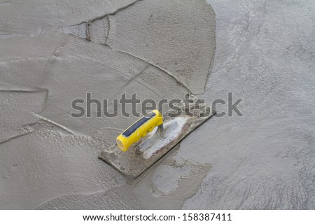 Trowel on fresh concrete at construction site  - stock photo