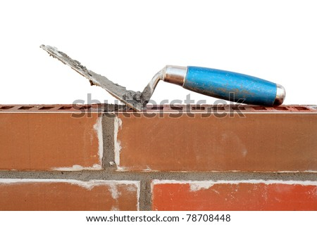 Trowel on new brick wall isolated on white - stock photo