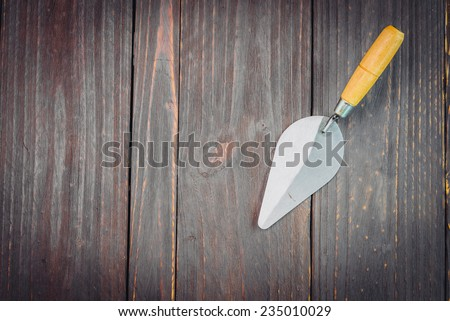 Trowel on wooden background - vintage effect style pictures - stock photo