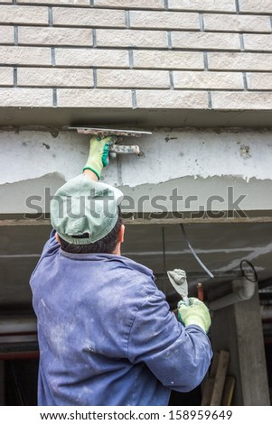Trowel spreading mortar on concrete wall, builder worker plastering - stock photo