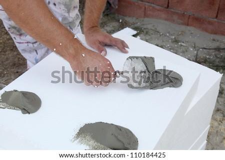 Trowel spreading mortar  on styrofoam insulation of wall - stock photo