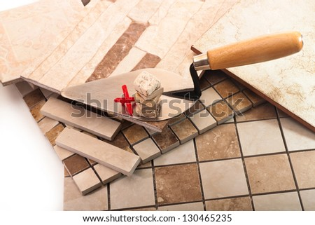 Trowel with a stack of tiles made �¢??�¢??of stone, and a red cross on a background of ceramic tiles - stock photo