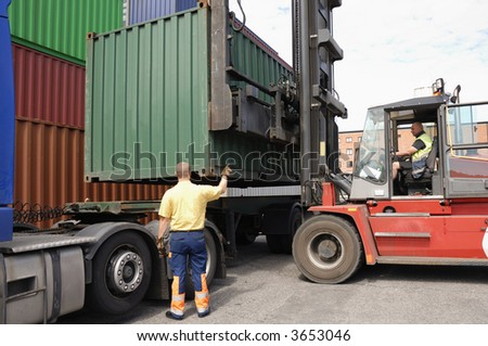 truck and driver loading truck with container, truck driver directing - stock photo