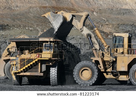 truck and excavator in work in mine - stock photo