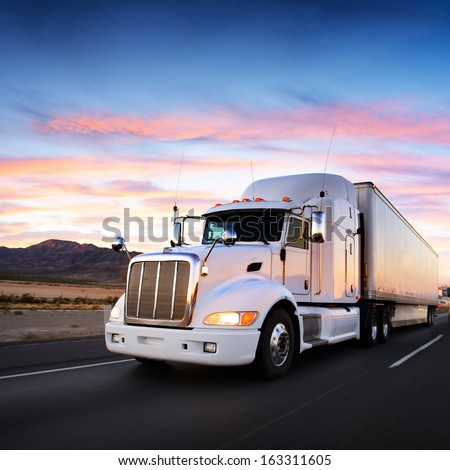 Truck and highway at sunset - transportation background - stock photo