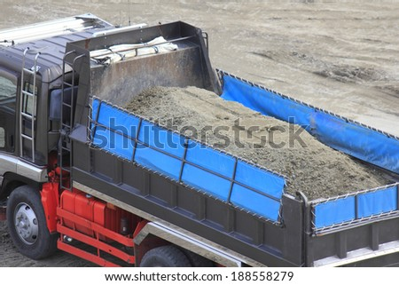 Truck carrying sand at construction site - stock photo