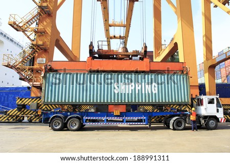 Truck crane unloading containers from the dock. - stock photo