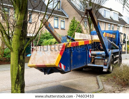 truck delivers waste container - stock photo