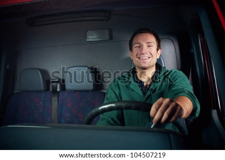 Truck driver holding wheel. Smiling at work