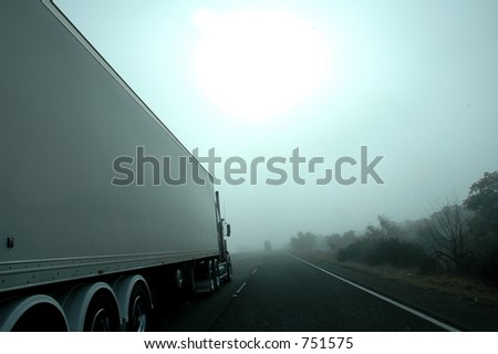 Truck driving in fog - stock photo