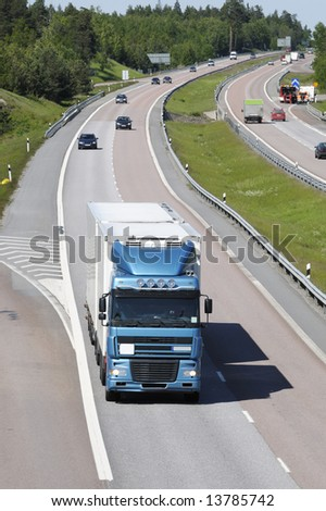 truck driving on highway surrounded by traffic, elevated shot - stock photo