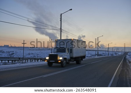 truck driving through landscape of coal mine and electric power plant in Siberia Russia - stock photo