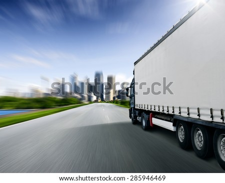 Truck driving towards big city - stock photo