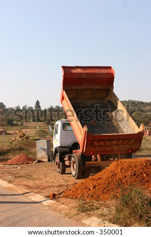Truck dumping sand at building site