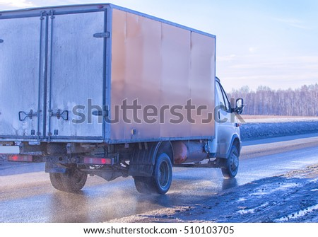 truck goes on winter highway in sunny day