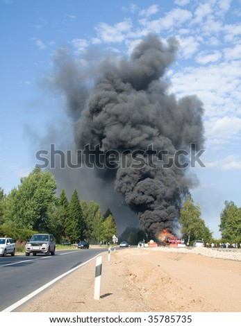 truck in fire with black smoke on the road - stock photo