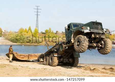 Truck is pulling element of pontoon bridge from river - stock photo