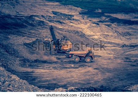 truck loader excavator moving earth and unloading into a dumper truck - stock photo
