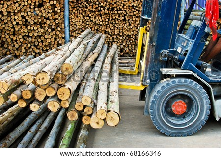 truck loading pile of wood in logs storage for construction or industrial work