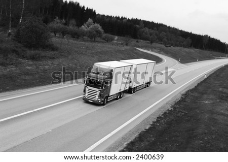 truck, lorry on highway in black and white - stock photo