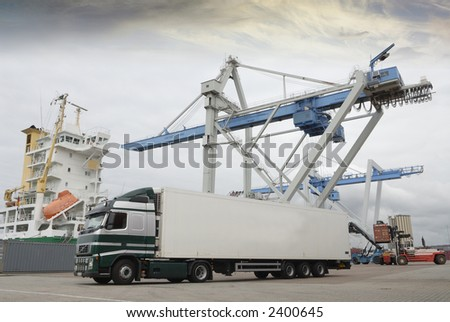 truck, lorry waiting in port for cargo by crane - stock photo