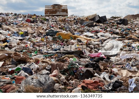 Truck managing garbage in a landfill site - stock photo