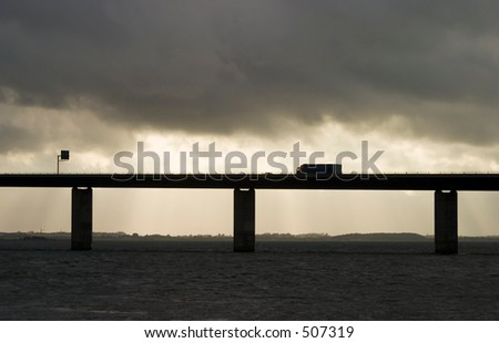 Truck on bridge over water in cloudy weather - stock photo