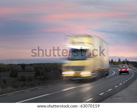 Truck on road in evening with purple sky - stock photo