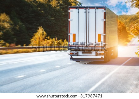 truck on the asphalt rural road on the sunset - stock photo
