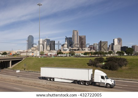 Truck on the highway with Dallas downtown skyline in the background. Texas, United States