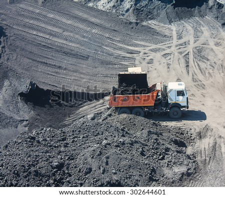 Truck on the loading of coal in coal mine - stock photo