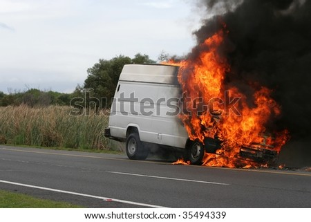 Truck or van burning creating large flames and smoke - stock photo