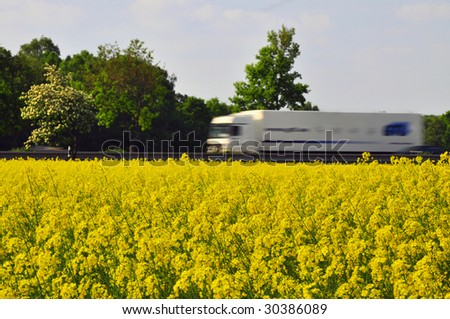 truck passing a rapeseed field as a symbol of alternative energy. - stock photo