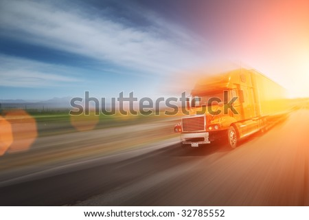 Truck speeding on freeway at sunset. Blurred motion. - stock photo