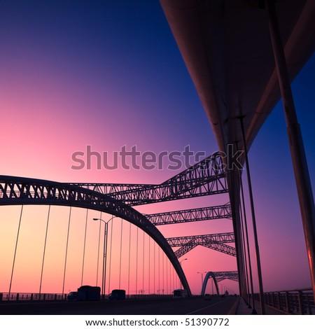 truck speeding through a bridge at sunset,motion blur. - stock photo