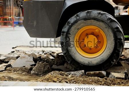 Truck tire on a broken asphalt at construction site in urban environment  - stock photo