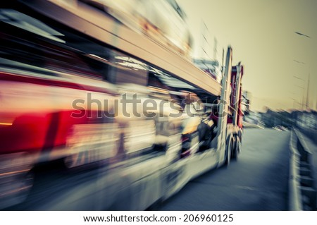 Truck transports cars, track in motion. - stock photo