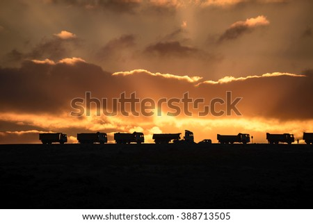 Truck traveling at sunset - stock photo