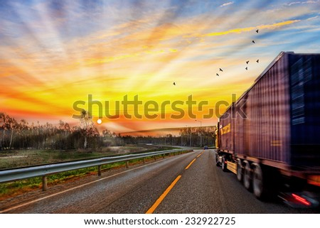 Truck traveling on road at sunrise - speed and delivery concept.  - stock photo