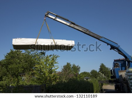 Truck unloading goods in allotment at summertime. - stock photo